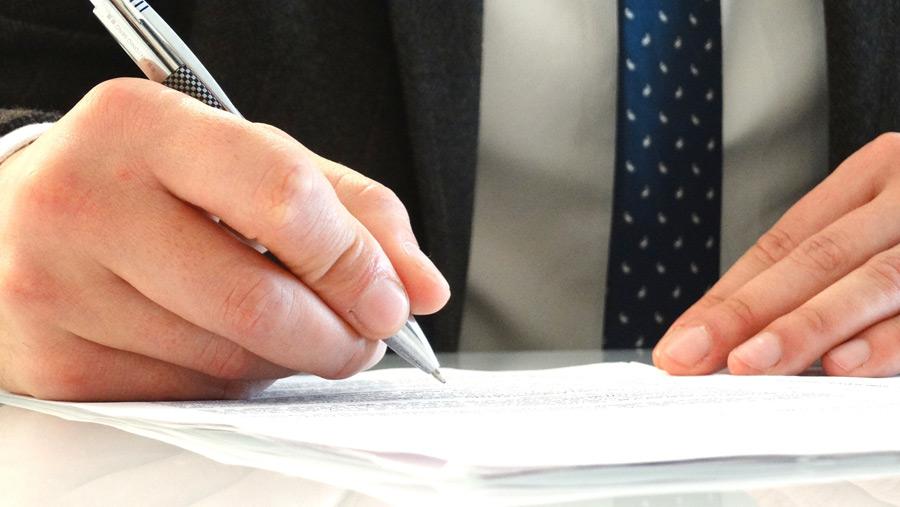 フリー写真 書類にサインしているビジネスマンの手元
