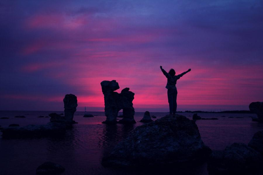 フリー写真 日暮れの海岸と岩の上に立つ人物