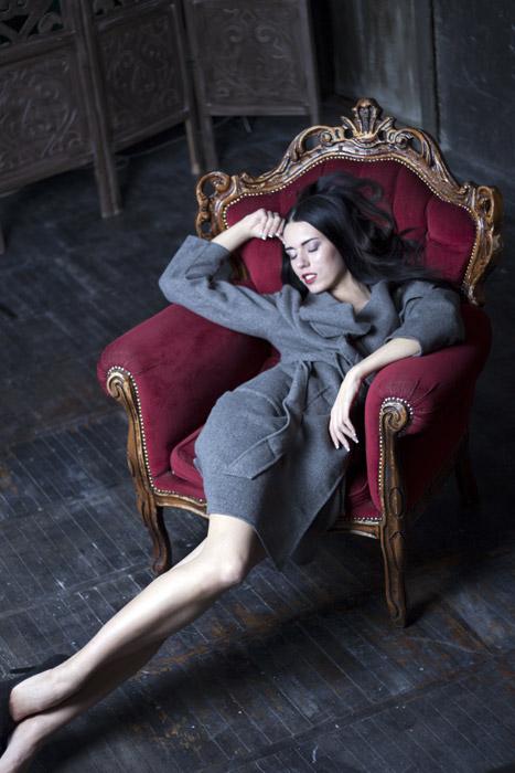 フリー写真 コート姿で椅子の上で寝ている外国人女性