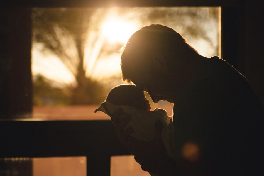 フリー写真 夕日と赤ちゃんと額をつける父親
