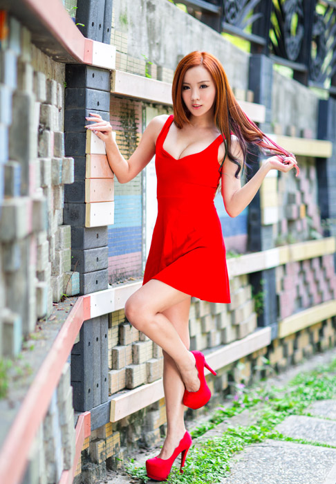 フリー写真 壁に手をついて片足を上げる女性