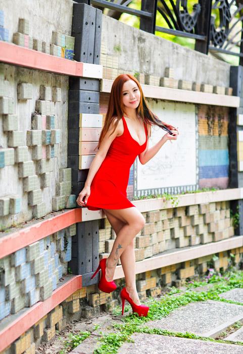 フリー写真 赤いドレス姿で髪の毛の先を持っている女性