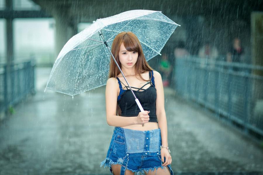 フリー写真 傘を差して雨の中に立つ女性