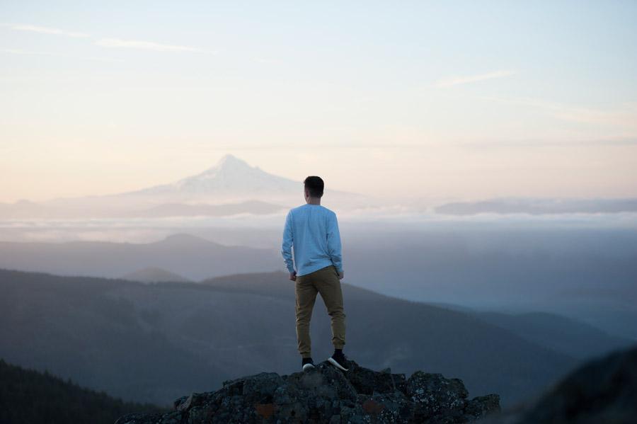 フリー写真 岩の上に立って景色を眺める男性とフッド山の風景