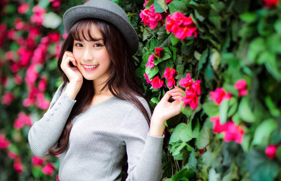フリー写真 花の壁の前でボーラー帽を被る女性
