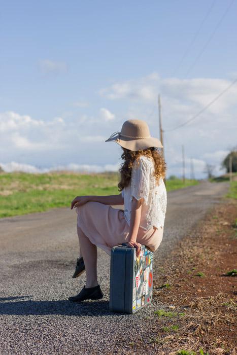 フリー写真 旅行鞄に腰掛けながら通りかかる車を待つ女性