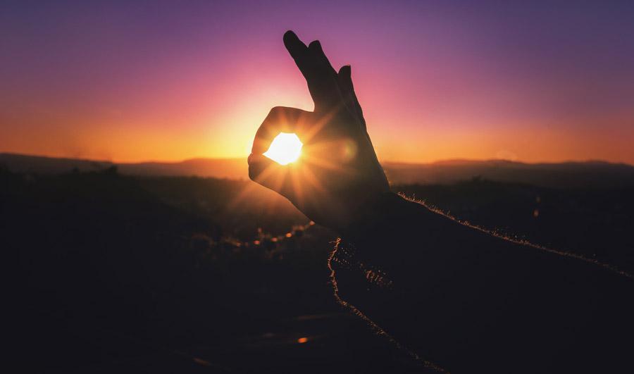 フリー写真 親指と人差し指の輪の中の夕日