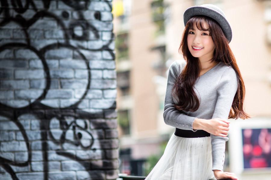 フリー写真 落書きされた壁の前で微笑む女性
