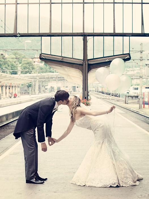 フリー写真 駅のプラットホームでキスをしている新郎新婦