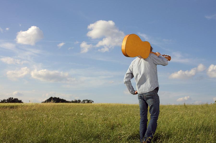 フリー写真 草原でギターを担ぐ男性の後ろ姿