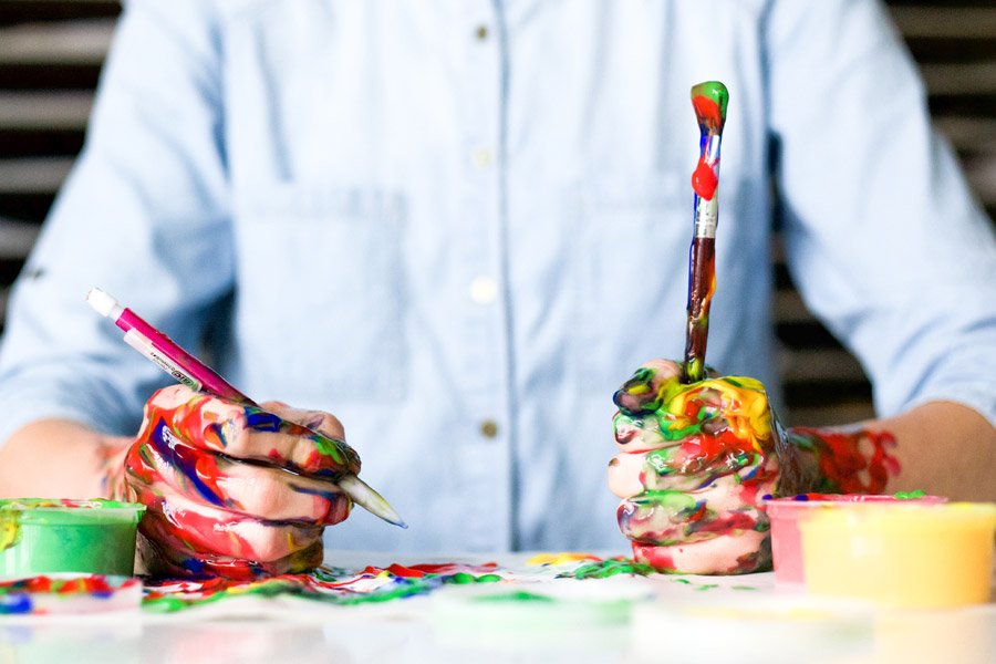 フリー写真 ペンと筆を持っている絵の具まみれの手