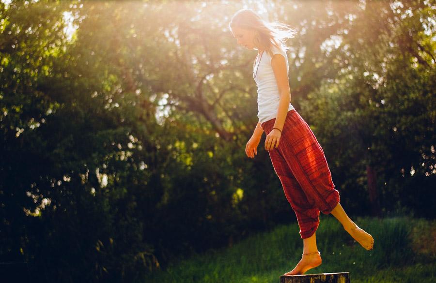 フリー写真 切り株の上で片足を上げて爪先立ちする女性
