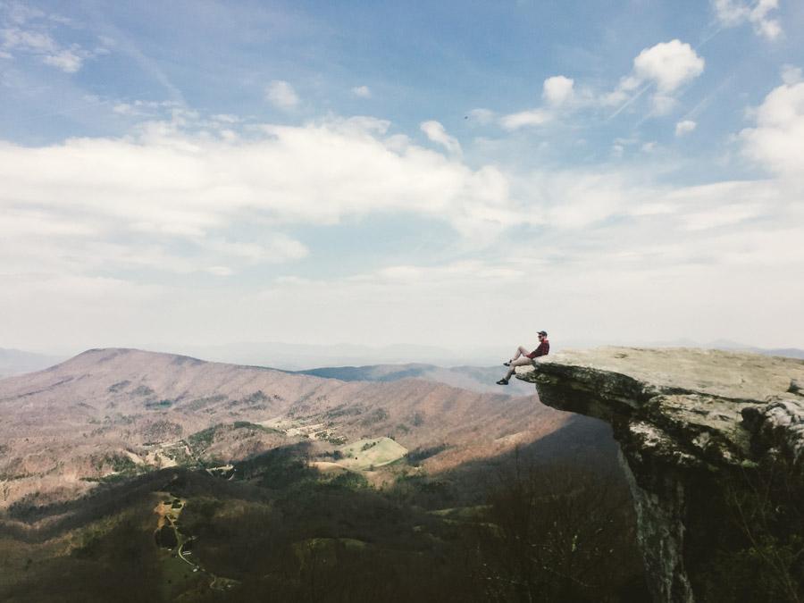 フリー写真 崖の先端に座って景色を眺める男性