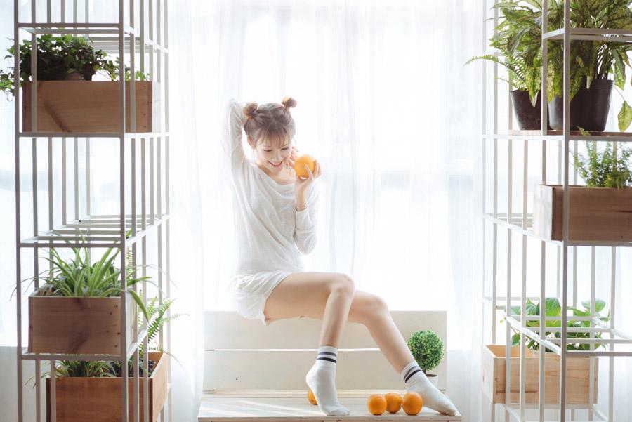 フリー写真 オレンジとベンチの背もたれの上に座る女性