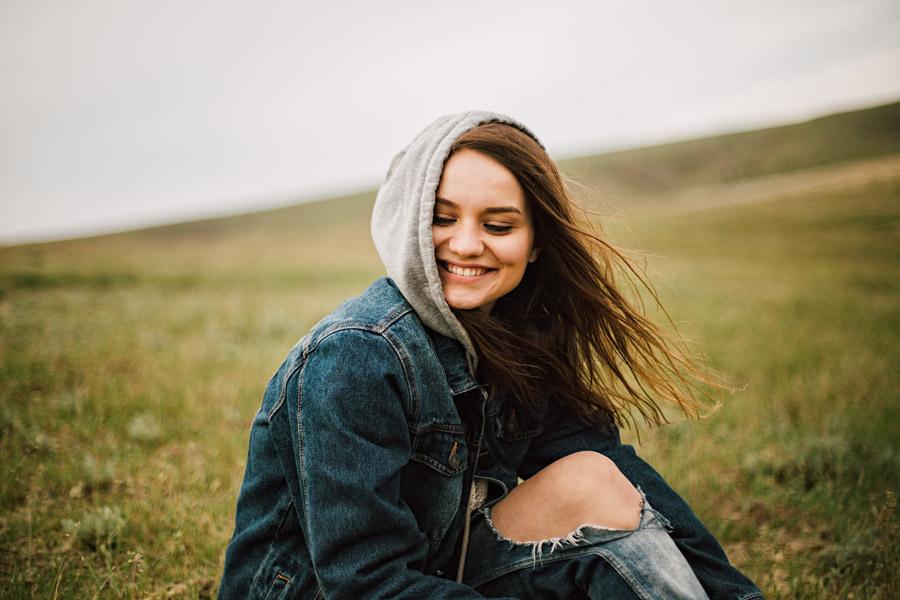 フリー写真 草原に座っている笑顔の外国人女性