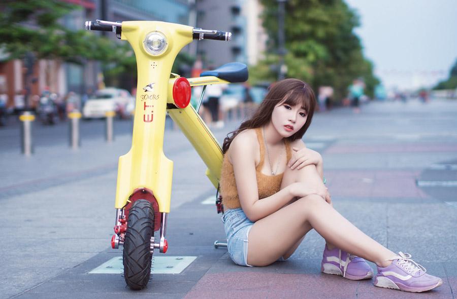 フリー写真 電動バイクの前に座り込む女性