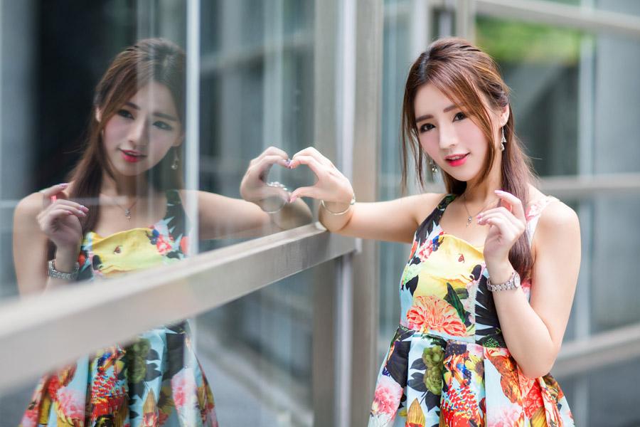 フリー写真 窓に映る自分の姿と手でハートを作る女性