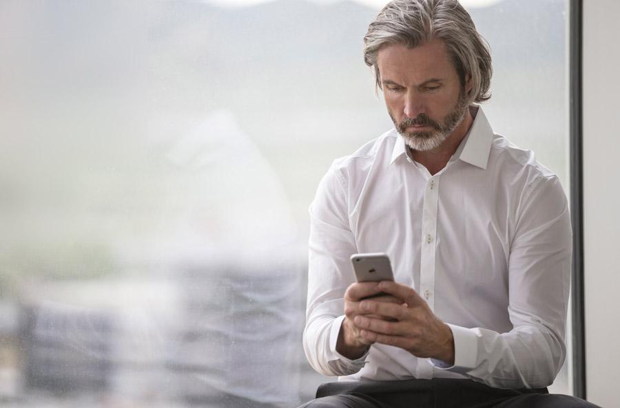 フリー写真 窓辺に座ってスマホを見ているビジネスマン