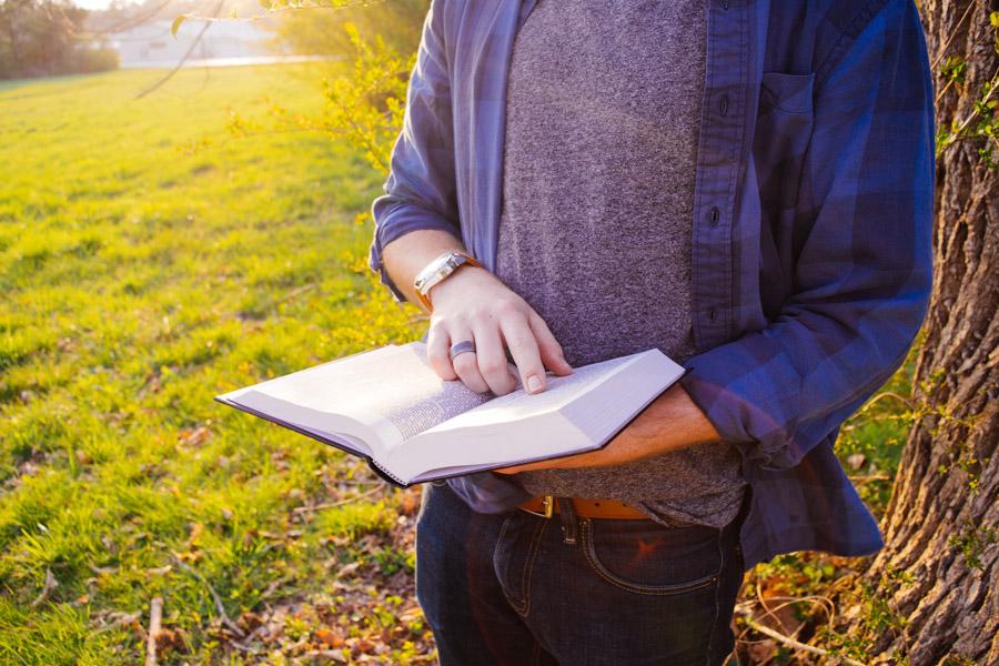 フリー写真 立ながら本を読んでいる男性