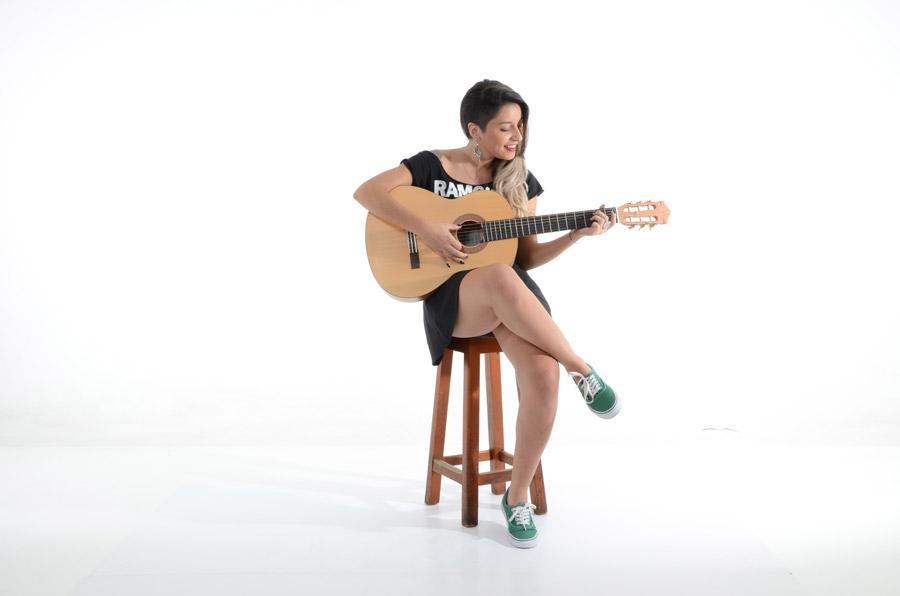 フリー写真 白背景と椅子に座ってギターを弾く外国人女性