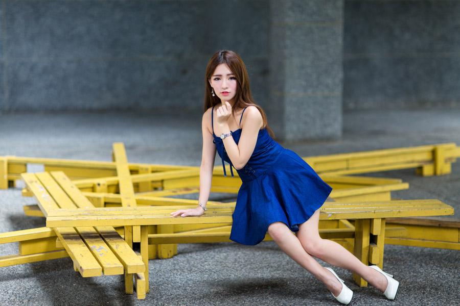 フリー写真 青いワンピース姿でベンチに座っている女性