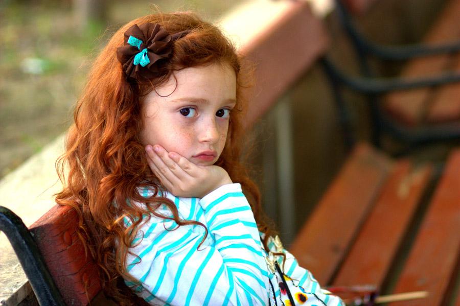 フリー写真 ベンチに座って頬杖をついている外国の女の子