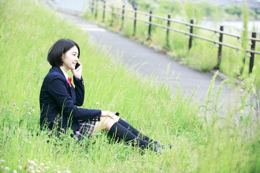 フリー写真 草むらに座って携帯電話で話ししている女子高生