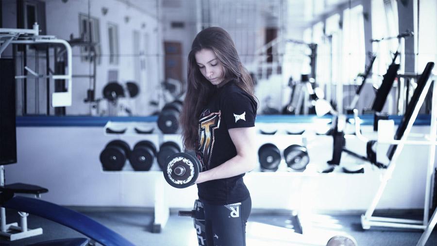 フリー写真 トレーニングジムでダンベルを上げる外国人女性