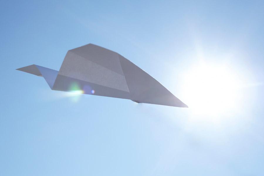 フリー写真 大空に飛ぶ紙飛行機と太陽の光