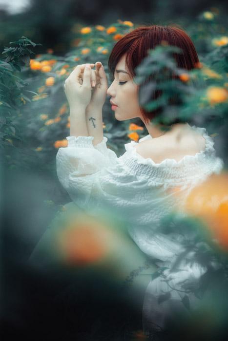 フリー写真 オレンジ色の花と目を閉じている女性の横顔