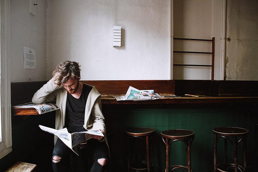 フリー写真 頭を抱えながら新聞を読んでいる外国人男性