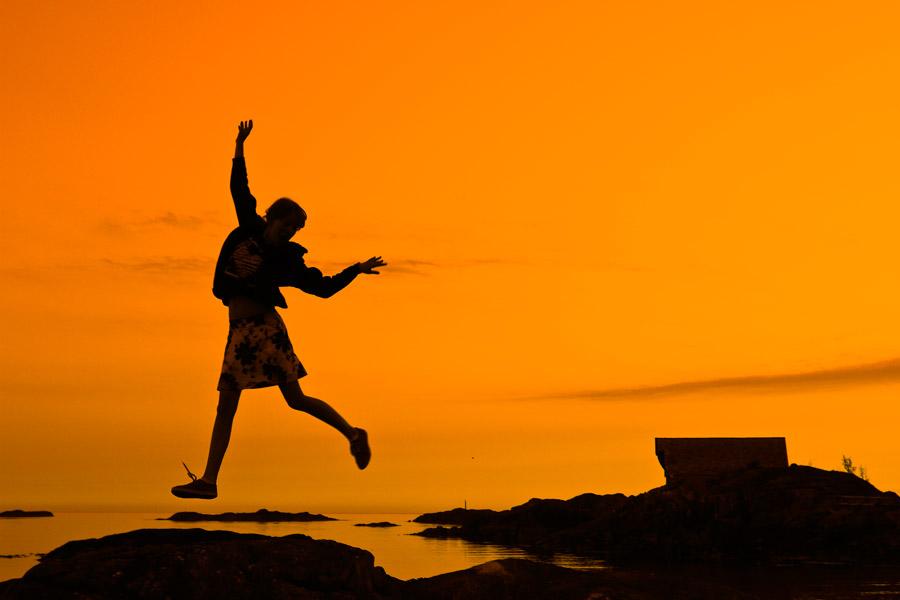 フリー写真 夕焼けと岩の上を飛び跳ねる女の子