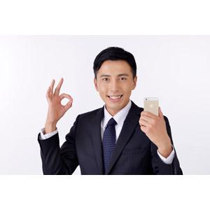 フリー写真, 人物, 男性, アジア人男性, 日本人, 男性(00016), 職業, 仕事, ビジネス, ビジネスマン, サラリーマン, メンズスーツ, 白背景, OKサイン, スマートフォン(スマホ), 携帯電話, 成功