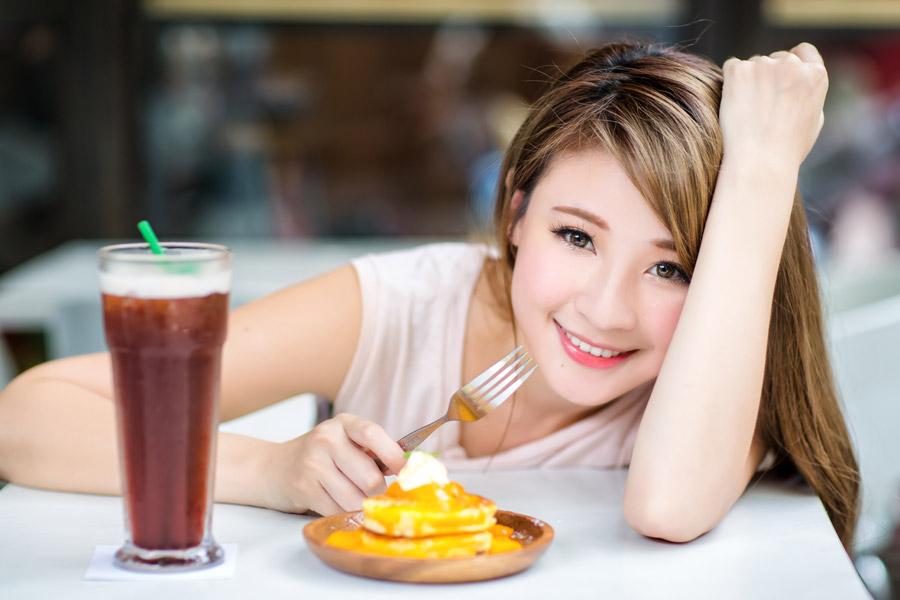 フリー写真 パンケーキと飲み物の前の女性