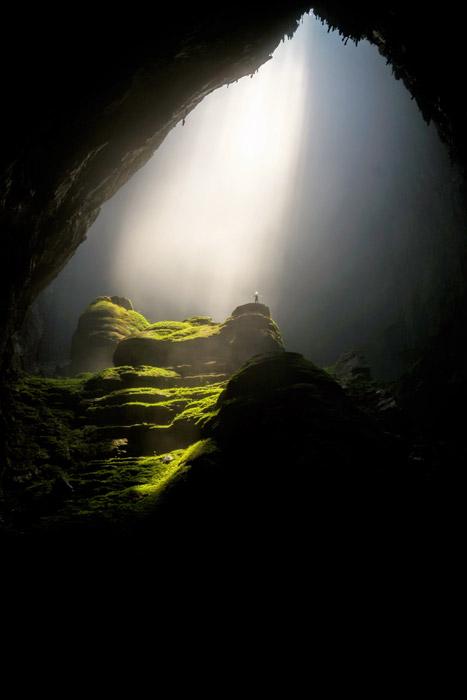 フリー写真 ソンドン洞窟に射し込む光と手を広げる人物