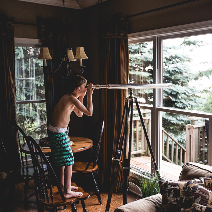 フリー写真 部屋の中で望遠鏡を覗く男の子