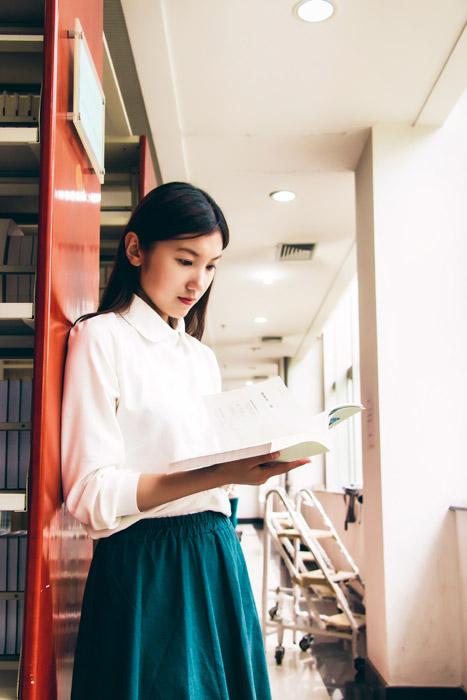 フリー写真 図書館で本を読む女子学生