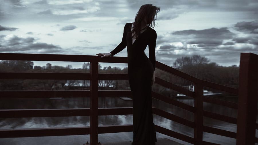 フリー写真 ドレス姿で手すりにの前に立つ外国人女性