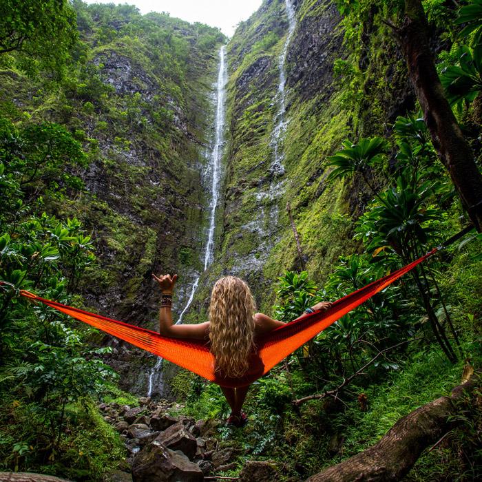 フリー写真 滝とハンモックでくつろぐ外国人女性の後ろ姿