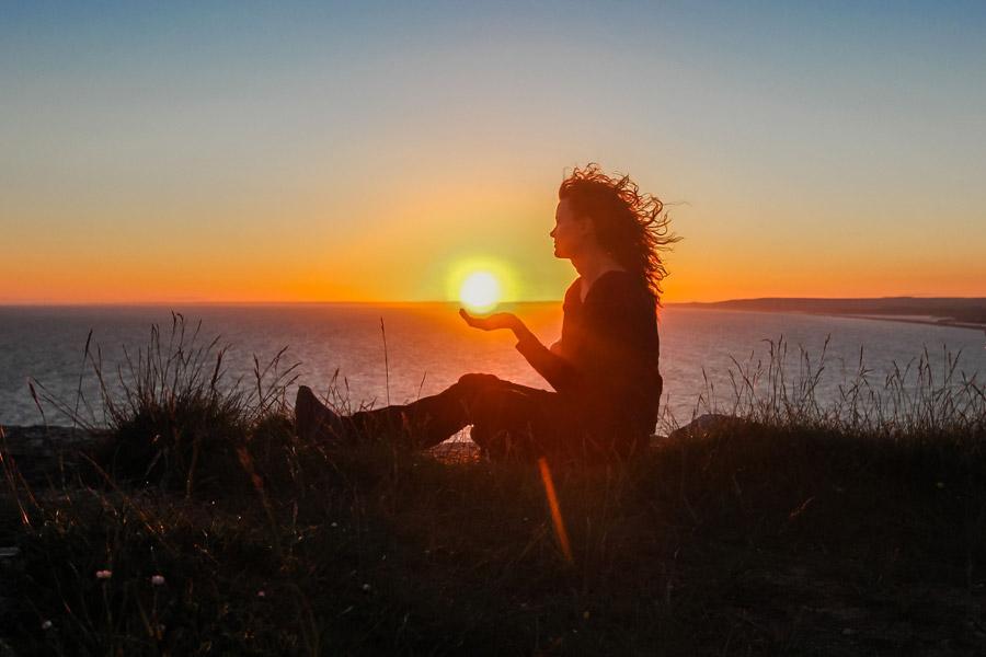 フリー写真 手の上に夕日をのせる外国人女性