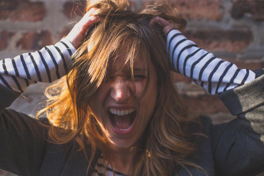 フリー写真 頭を抱えて叫ぶ外国人女性