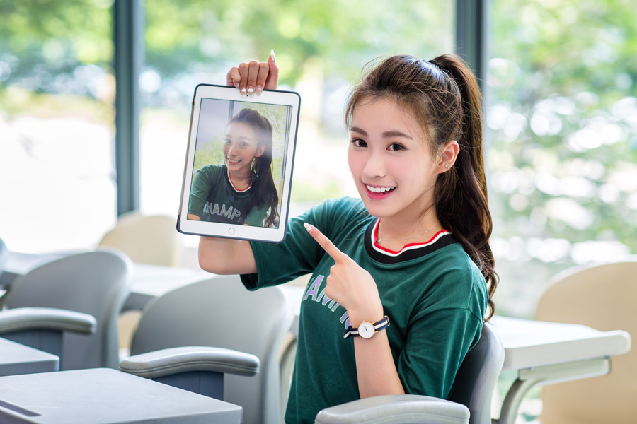フリー写真 タブレットPCを指差す女子大学生