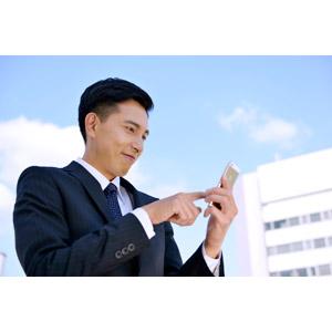 フリー写真, 人物, 男性, アジア人男性, 日本人, 男性(00016), 職業, 仕事, ビジネス, ビジネスマン, サラリーマン, メンズスーツ, 青空, スマートフォン(スマホ)