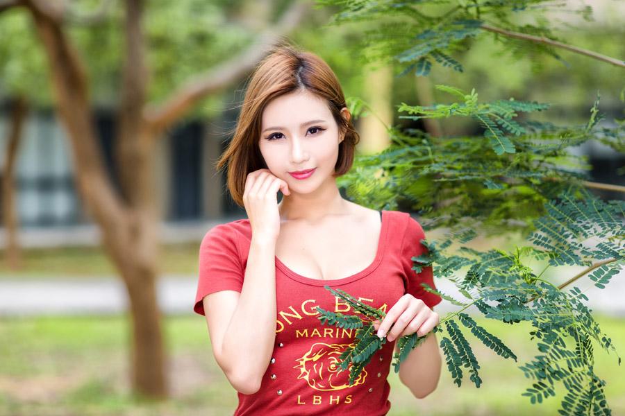 フリー写真 木の葉と頬に手を当てるショートヘアの女性