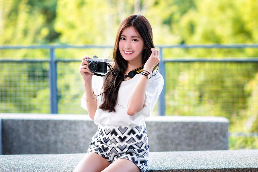 フリー写真 カメラを持ってベンチに座る女性