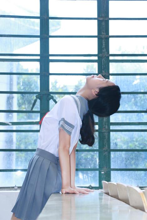 フリー写真 セーラー服姿で天井を見上げる女子学生