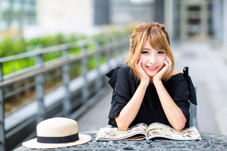フリー写真 麦わら帽子と雑誌と両手で頬杖をつく女性
