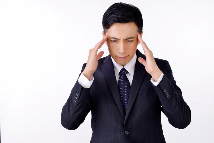 フリー写真 こめかみを押さえる頭痛のサラリーマン男性