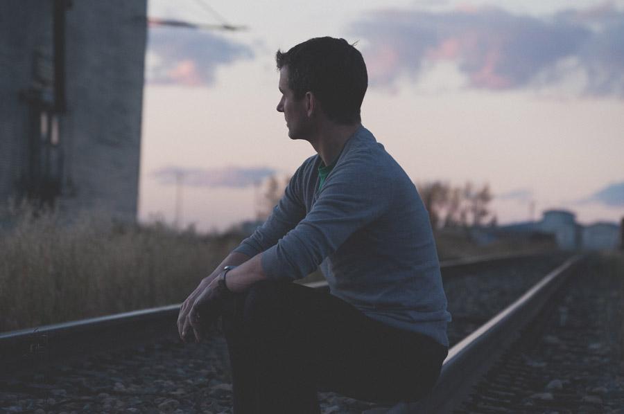 フリー写真 線路の上に座る外国人男性