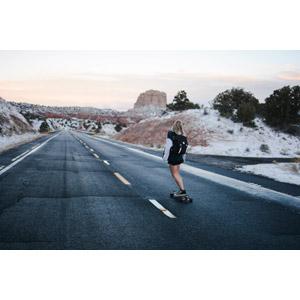 フリー写真, 人物, 女性, 外国人女性, スケートボード(スケボー), スポーツ, 後ろ姿, リュックサック(ナップサック), 人と風景, 道路, 荒野, 雪, アメリカの風景